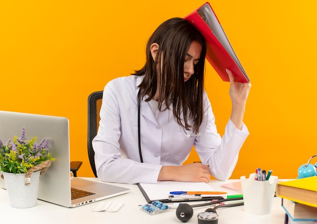 Giovani donne medico in camice bianco con lo stetoscopio che tiene la cartella sopra la sua testa che sembra stanco e oberato di lavoro seduto al tavolo con laptop e documenti oltre la parete arancione