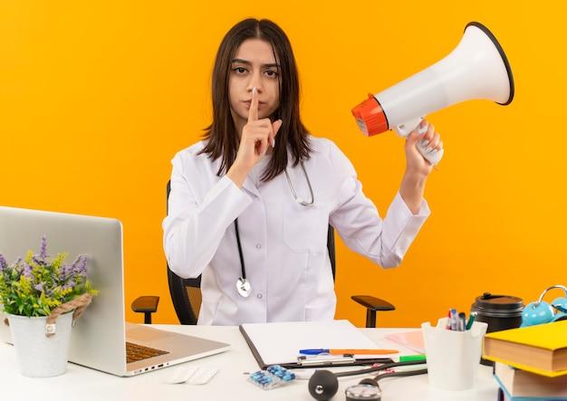 Giovane medico femminile in camice bianco con lo stetoscopio che tiene il megafono che fa il gesto di silenzio con il dito sulle labbra seduto al tavolo con il computer portatile e documenti sopra la parete arancione
