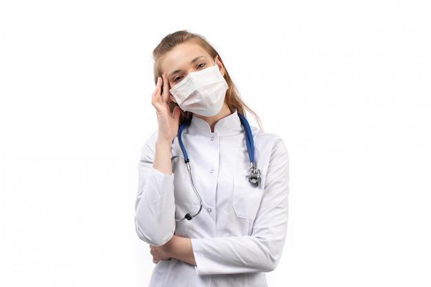 Giovane dottoressa in tuta medica bianca in maschera protettiva bianca stetoscopio pensando posa sul bianco
