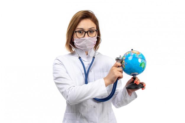 Giovane dottoressa in tuta medica bianca con stetoscopio in maschera protettiva bianca che tiene intorno al piccolo globo sul bianco