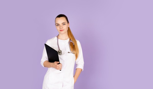 Young female doctor in white uniform with phonendoscope on her neck
