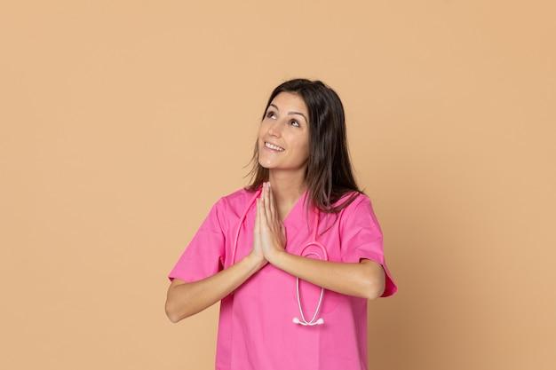 茶色の壁に身振りで示すピンクの制服を着た若い女性医師