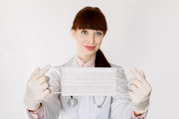白いコートの聴診器で笑顔の若い女性医師と笑みを浮かべて、ウイルス感染に対する保護フェイスマスクをカメラに見せて、洞窟-19、白い背景の上に立っています。手でマスクに焦点を当てる