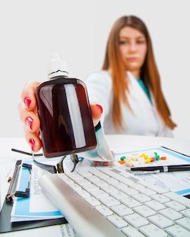 Молодая женщина-врач с бутылкой таблеток в руке