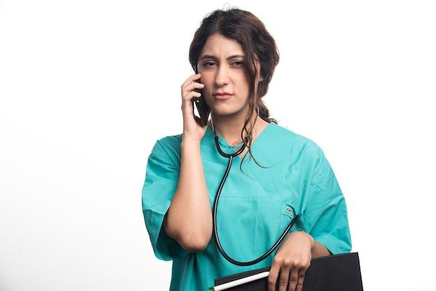 Молодая женщина-врач с буфером обмена и держа сотовый телефон на белой предпосылке. фото высокого качества
