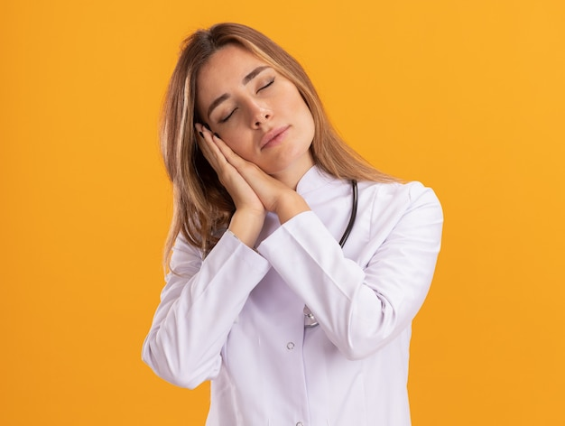 Young female doctor with closed eyes wearing medical robe with stethoscope showing sleep gesture isolated on yellow wall