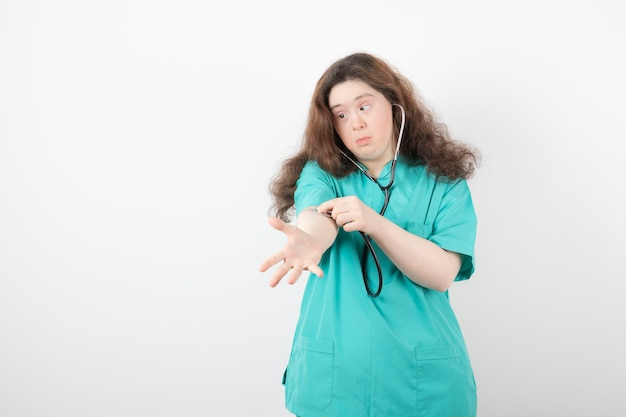 Young female doctor with down syndrome checking her pulse on white wall.