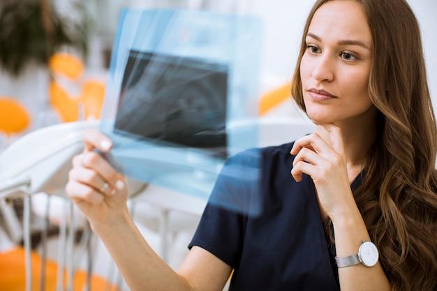 歯科医のオフィスでレントゲン写真を調べる保護手袋を持つ若い女性医師