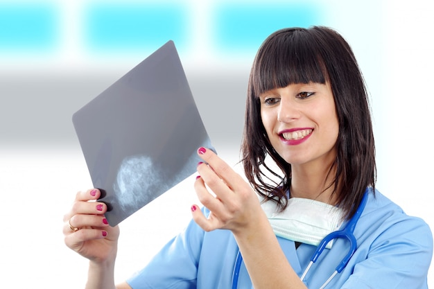 Young female doctor with stethoscope looking at patients x ray
