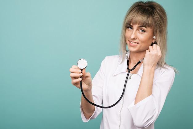 Молодая женщина-врач со стетоскопом на переднем плане. вырезать лицо, изолированное на синем пространстве