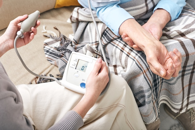 Young female doctor with tonometer measuring blood pressure of senior retired man covered by plaid while sitting on couch