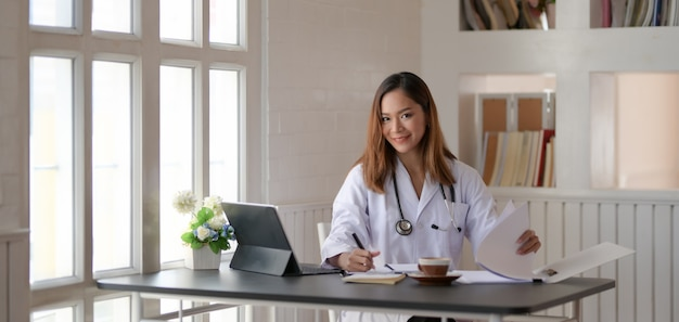Young female doctor working on medical charts and document