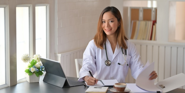 Young female doctor working with tablet and writing on paperwork in office room