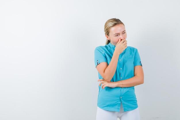 Giovane dottoressa che sbadiglia in uniforme medica, maschera e sembra assonnata