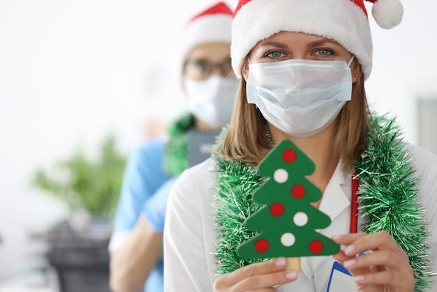 Молодые женщины-врачи в шапках санта-клауса и мишуре на шее держат елку