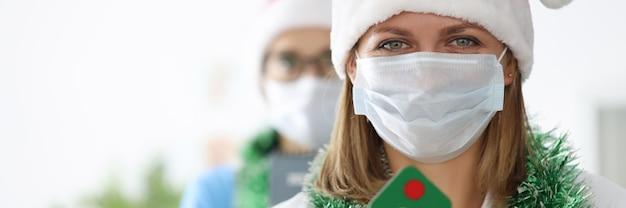 Молодые женщины-врачи в шляпах санта-клауса и мишуре на шее держат елку