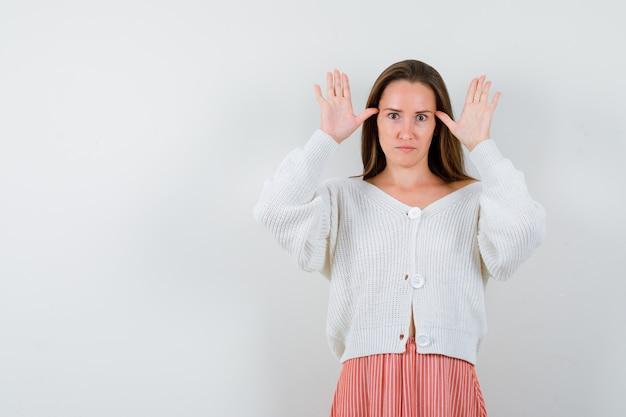 カーディガンとスカートで耳のジェスチャーをしている若い女性
