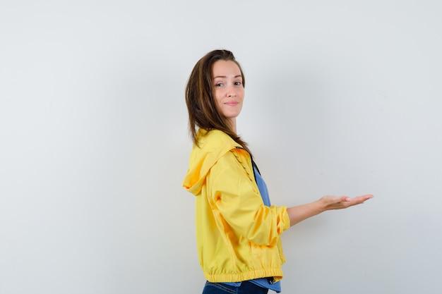 Giovane donna che fa gesto di benvenuto in maglietta, giacca e sembra sicura.