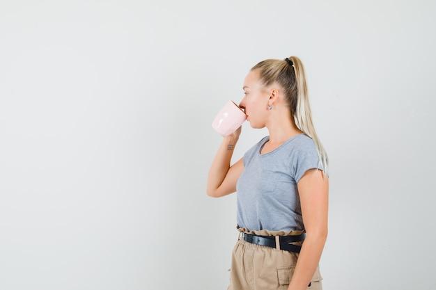 Giovane donna che beve il caffè in maglietta, pantaloni e dall'aspetto elegante. vista frontale.