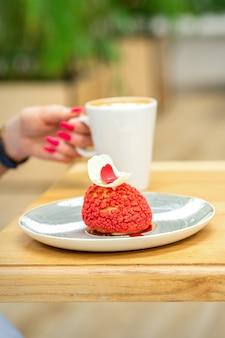 야외 카페에서 테이블에 앉아 케이크 한 조각으로 커피를 마시는 젊은 여성