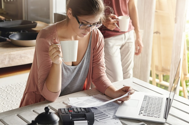 Young female drinking tea and studying bill in her hands, having frustrated look while managing family budget and doing paperwork, sitting at kitchen table with papers, calculator and laptop computer
