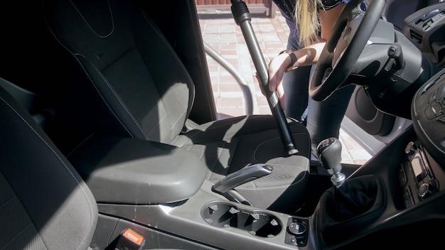Молодая женщина-водитель чистит и чистит сиденья пылесосом.
