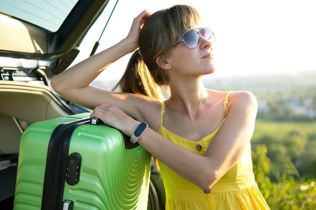 彼女の車の近くの緑のスーツケースに寄りかかって休んでいる若い女性ドライバー