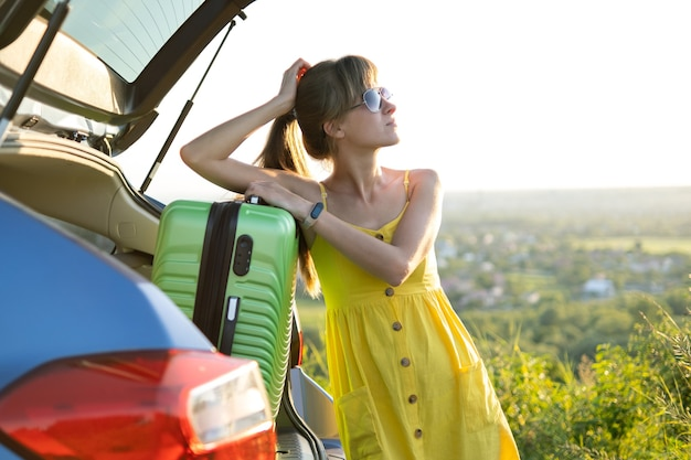 Young female driver having rest leaning on a suitcase in her car in summer field. travel and vacations concept.