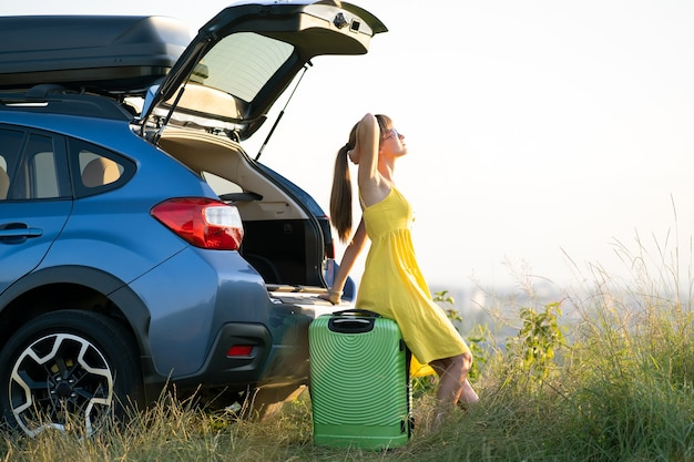 Young female driver having rest sitting on a suitcase near her car in summer field. travel and vacations concept.