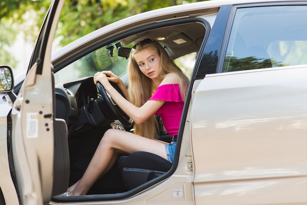 Young female driver in pink top