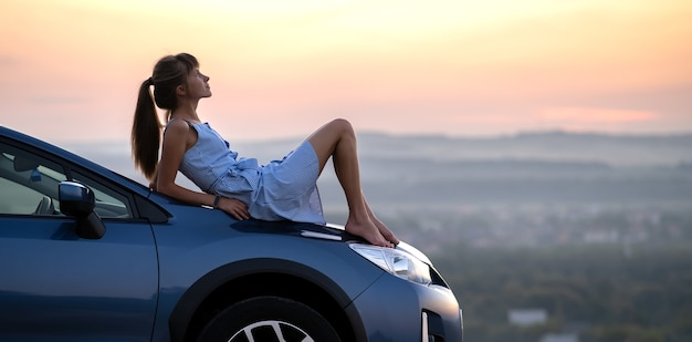Young female driver resting on hood of her car enjoying warm summer evening.