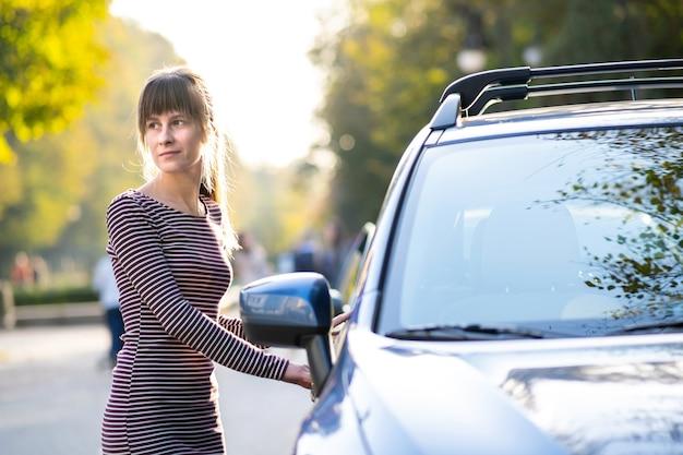 따뜻한 여름날을 즐기는 그녀의 차 근처에서 쉬고 있는 젊은 여성 운전자. 여행 및 도주 개념입니다.