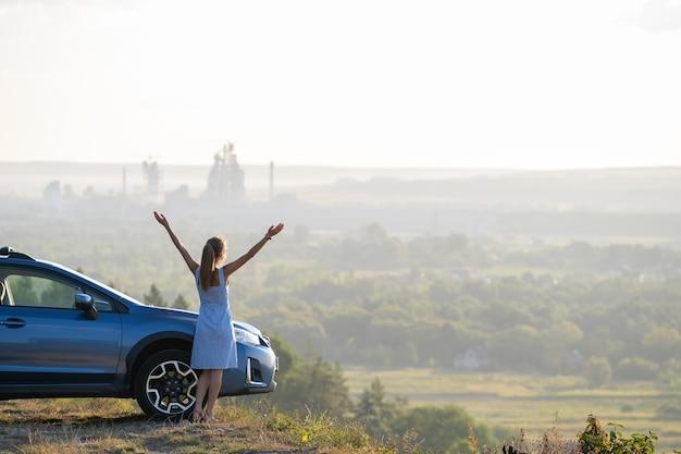 Молодая женщина-водитель отдыхает возле своей машины, наслаждаясь теплым летним вечером. концепция путешествия и бегства.