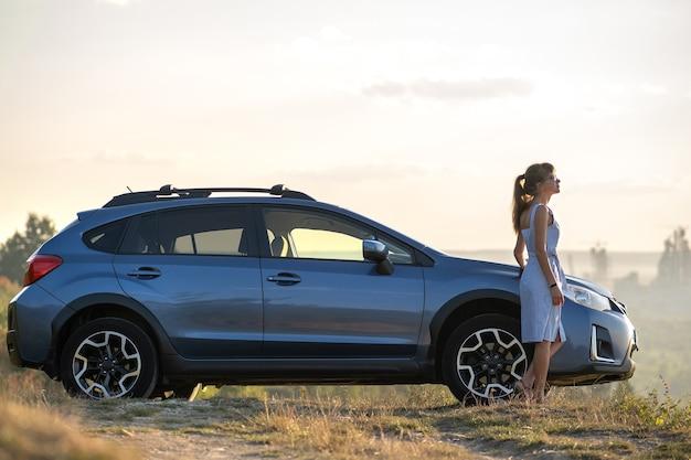 따뜻한 여름 저녁을 즐기는 그녀의 차 근처에서 쉬고 있는 젊은 여성 운전자. 여행 및 도주 개념입니다.