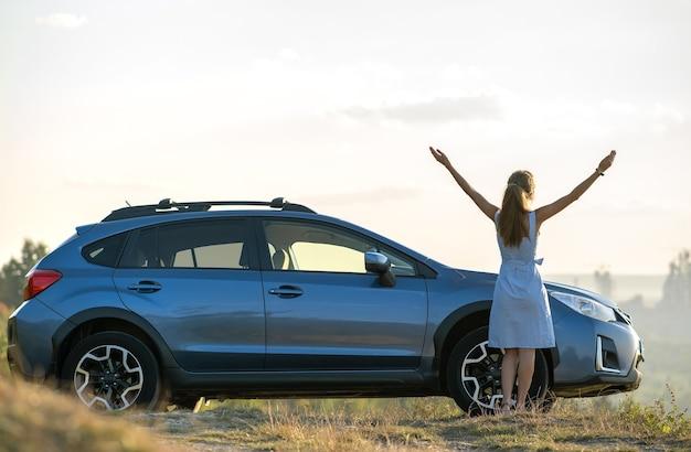 暖かい夏の夜に手を上げて車の近くで休んでいる若い女性ドライバー。旅行先のコンセプト。