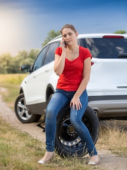젊은 여성 운전자가 들판에서 다음 고장난 차에 앉아 전화로 이야기