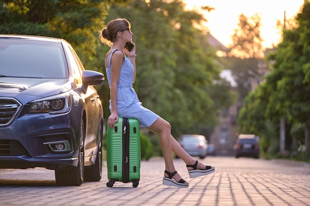 Молодая женщина-водитель сидит на чемодане возле своей машины, разговаривает по телефону на городской улице летом.