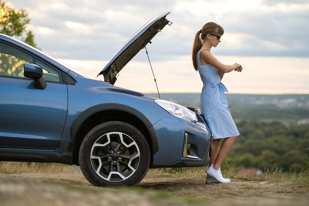 Молодая женщина-водитель, стоящая возле разбитой машины с открытым капотом, осматривает двигатель своего автомобиля и ждет помощи.