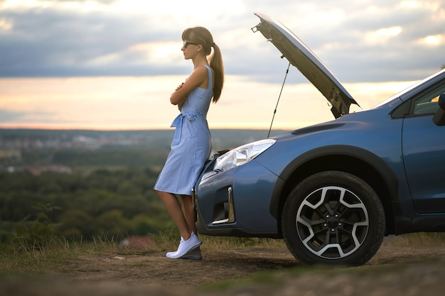 Young female driver standing near a broken car with open up hood inspecting her vehicle engine and waiting for help.