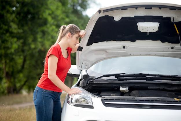田舎で壊れた車のために動揺している若い女性ドライバー