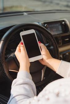 자동차에서 터치 스크린 스마트폰과 gps 내비게이션을 사용하는 젊은 여성 운전자.