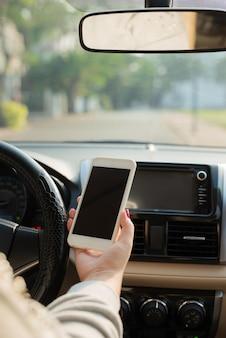 タッチスクリーンのスマートフォンと車の中でハンドルを握っている手を使用している若い女性ドライバー。