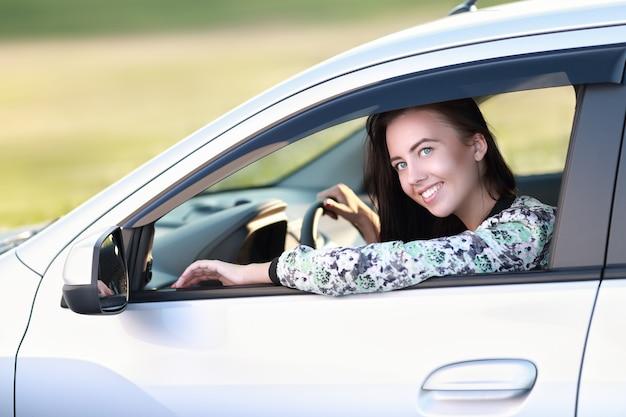그녀의 새 차 또는 운전 면허증에 대해 행복하게 운전하는 젊은 여성