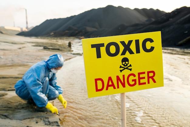 Молодая женщина-эколог в защитном комбинезоне, перчатках и респираторе отбирает пробы и изучает характеристики токсичной воды на берегу реки