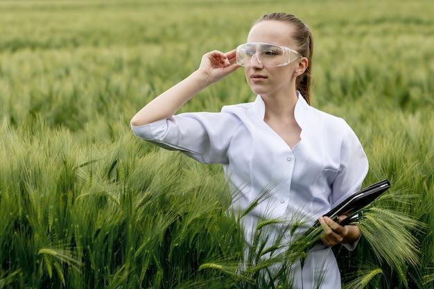 Молодой женский ученый-эколог в очках, стоящих в зеленом поле и работающих на стеклянном прозрачном экране.