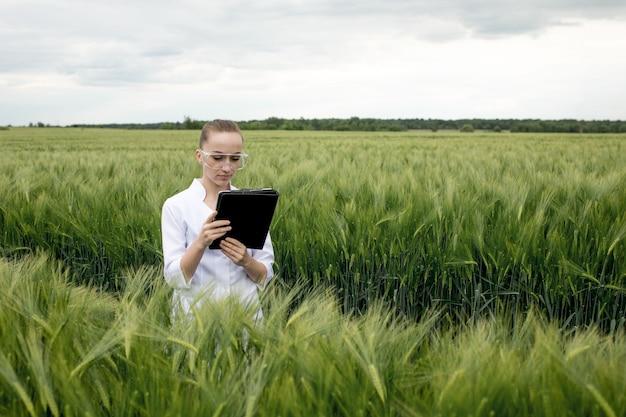 Молодой ученый-эколог женского пола в очках, стоящих в зеленом поле и работающих на стеклянном прозрачном экране.