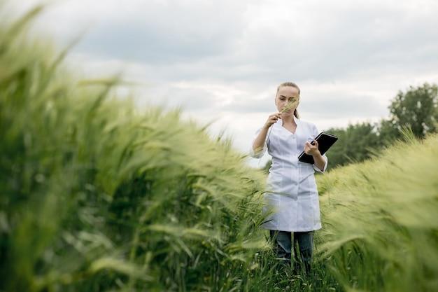 Молодая женщина-ученый-эколог в очках стоит в зеленом поле и работает