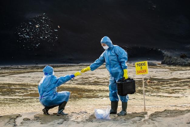 Молодая женщина-эколог берет колбу с образцом загрязненной воды или почвы из руки своего коллеги во время исследования на опасной территории