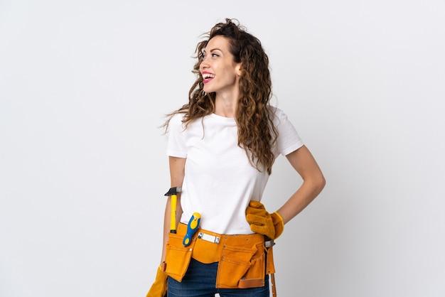 엉덩이에 팔을 포즈와 미소 흰 벽에 고립 된 젊은 여성 전기