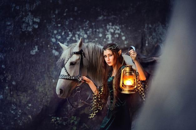 Молодая женщина-эльф, идущая со своей лошадью, держащая фонарь